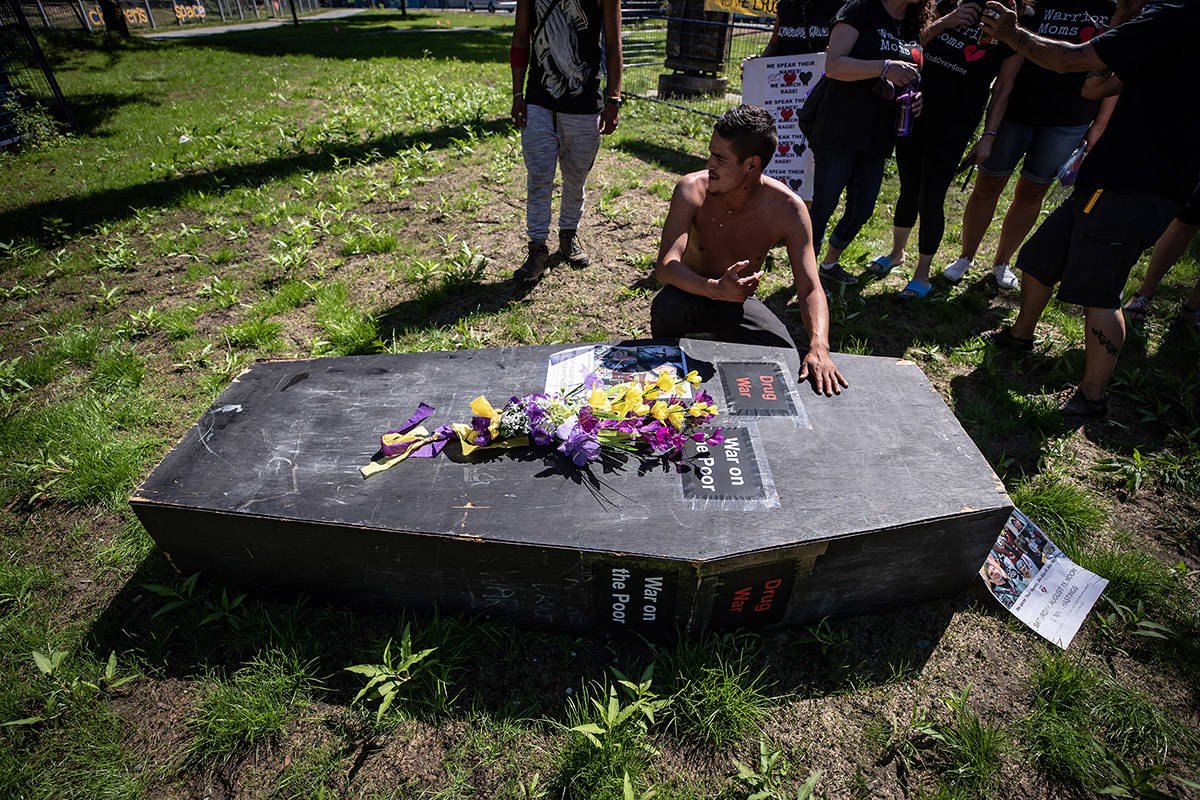 A man pauses at a coffin after carrying it during a memorial march to remember victims of overdose deaths in Vancouver on Saturday, August 15, 2020. THE CANADIAN PRESS/Darryl Dyck