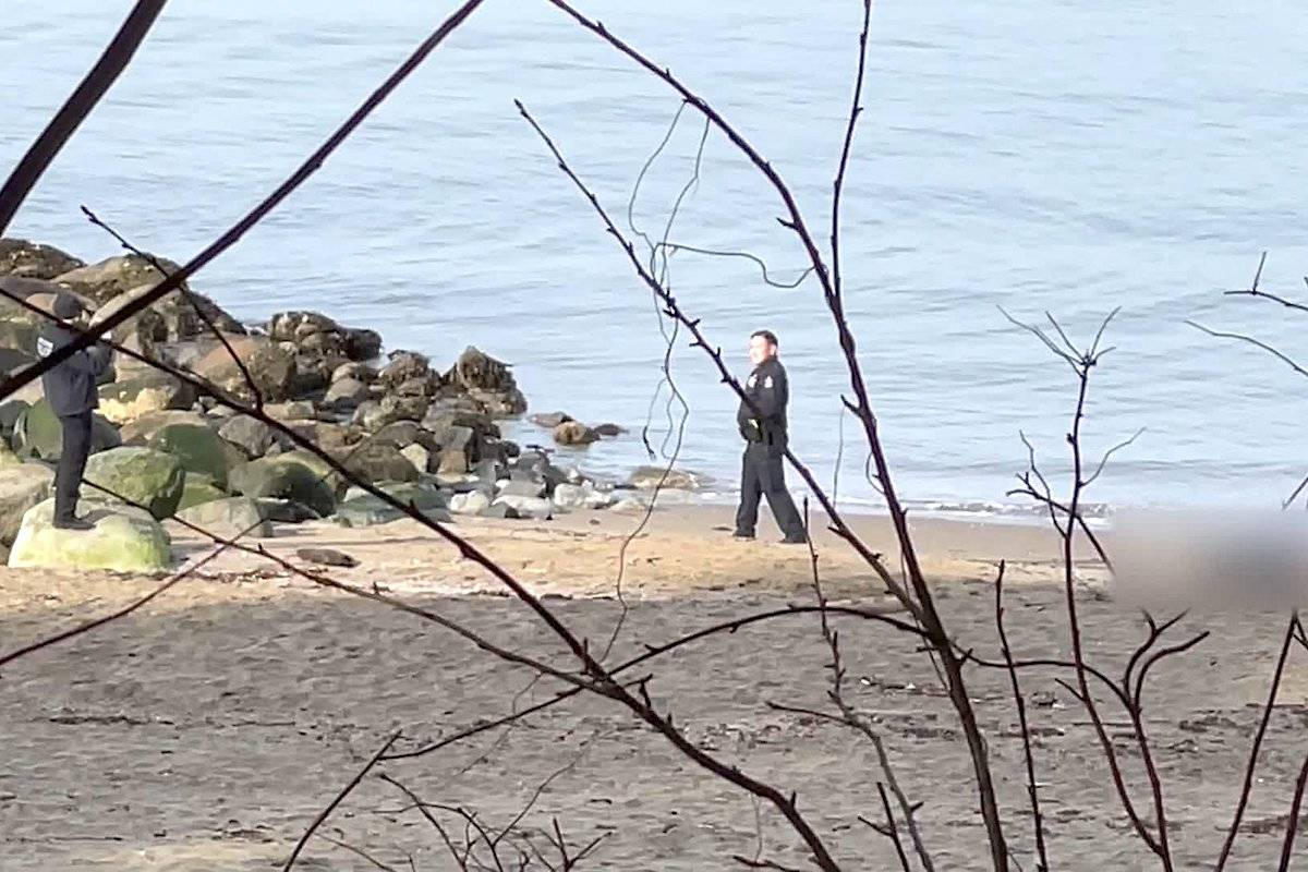 An investigation is underway after two VPD officers were recorded posing for pictures near a dead body at Third Beach on Feb. 24. (Screen grab/Zachary Ratcliff)