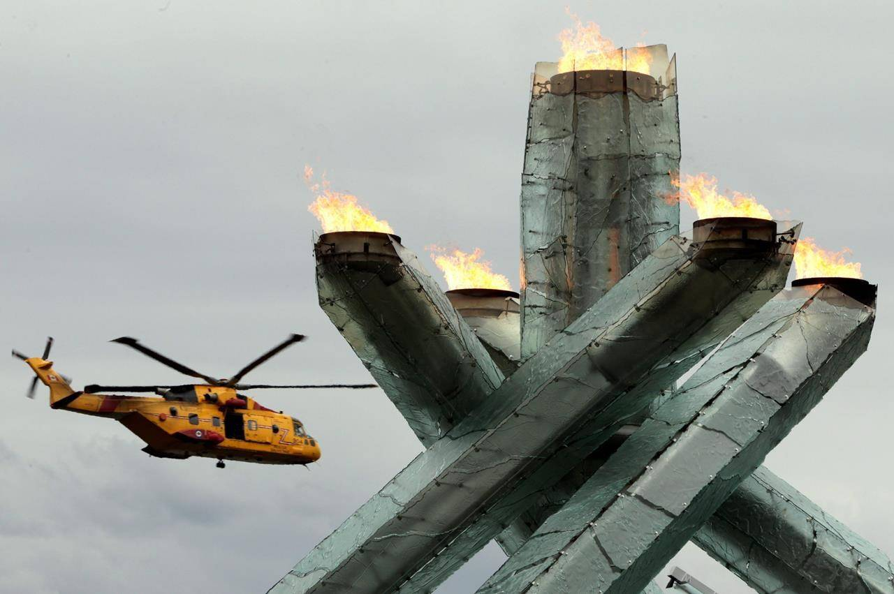 A Canadian Forces CH-149 Cormorant helicopter flies past the Olympic cauldron as it burns during Canada Day festivities in Vancouver, B.C., Thursday July 1, 2010. The owner of a scallop trawler that caught fire at sea south of Yarmouth, N.S., Tuesday night says all crew members are safely off the boat. THE CANADIAN PRESS/Darryl Dyck