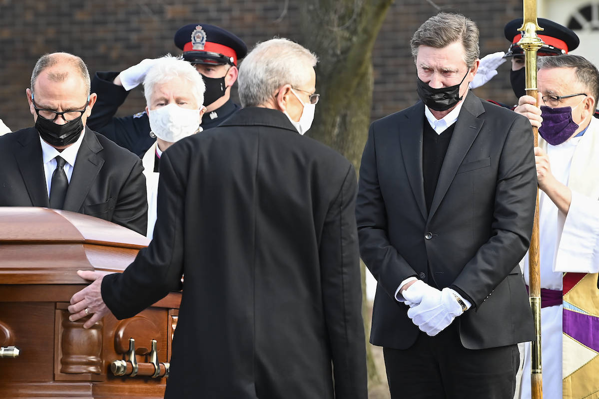 Hockey hall-of-fame legend Wayne Gretzky, right, watches the casket of his father, Walter Gretzky, as it is carried from the church during a funeral service in Brantford, Ont., Saturday, March 6, 2021. HE CANADIAN PRESS/Nathan Denette