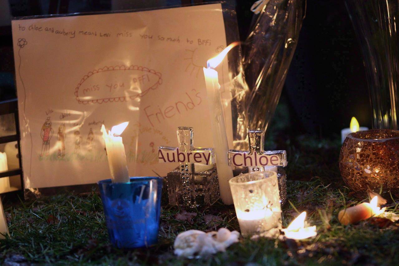 Pictures and notes in from friends and classmates make up a memorial in support and memory of Aubrey Berry, 4, and her sister Chloe, 6, during a vigil held at Willows Beach in Oak Bay, B.C., on December 30, 2017. THE CANADIAN PRESS/Chad Hipolito