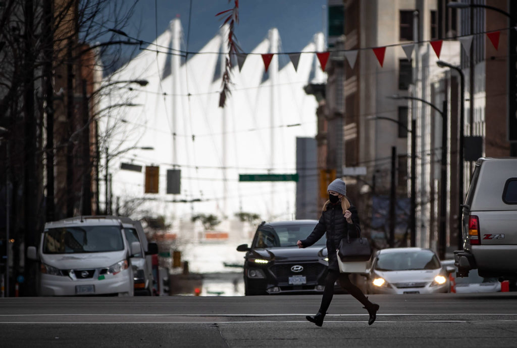 A pedestrian wearing a face mask to curb the spread of COVID-19 sprints across a street in Vancouver, on Monday, March 8, 2021. THE CANADIAN PRESS/Darryl Dyck