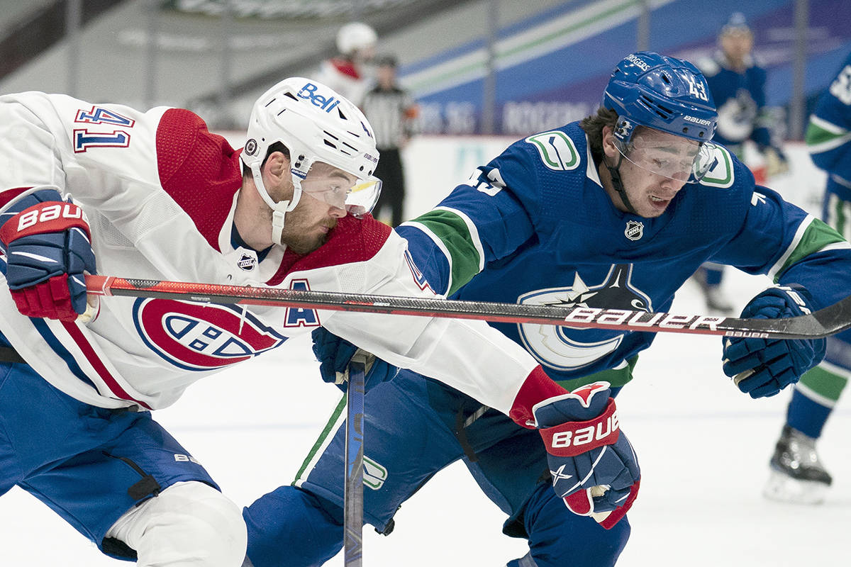 Montreal Canadiens right wing Paul Byron (41) fights for control of the puck with Vancouver Canucks defenceman Quinn Hughes (43) during first period NHL action in Vancouver, Monday, March 8, 2021. THE CANADIAN PRESS/Jonathan Hayward