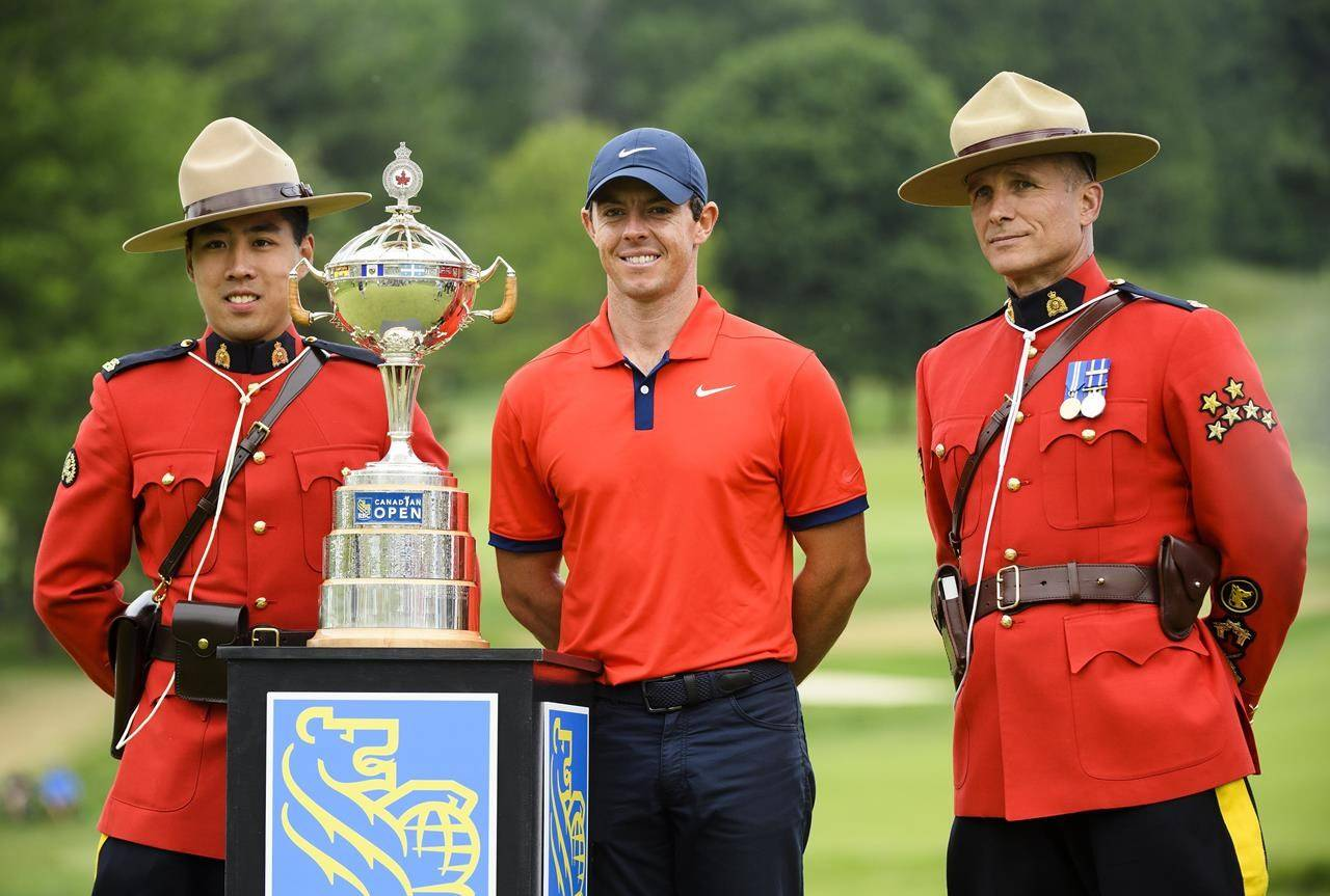 Rory McIlroy of Northern Ireland, centre, poses with Royal Canadian Mounted Police officers with the Championship trophy after winning the 2019 Canadian Open golf championship in Ancaster, Ont., on Sunday, June 9, 2019. The 2021 Canadian Open is set to be cancelled because of COVID-19 border restrictions. THE CANADIAN PRESS/Nathan Denette