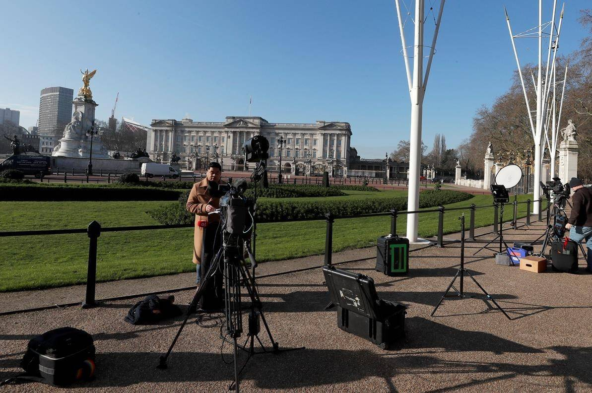 Journalists prepare in front of Buckingham Palace in London, Tuesday, March 9, 2021. Britain's royal family is absorbing the tremors from a sensational television interview by Prince Harry and the Duchess of Sussex, in which the couple said they encountered racist attitudes and a lack of support that drove Meghan to thoughts of suicide. (AP Photo/Frank Augstein)