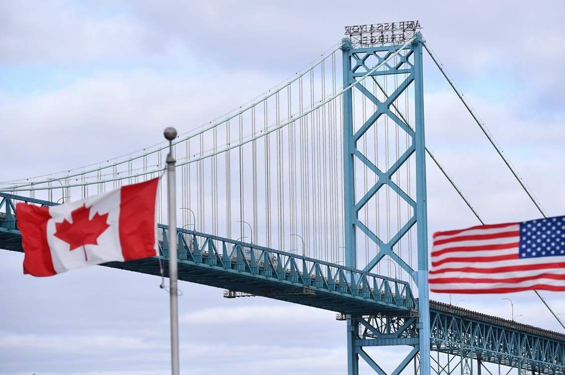 Canadian and American flags fly near the Ambassador Bridge at the Canada-USA border crossing in Windsor, Ont. on Saturday, March 21, 2020. The Organization for Economic Co-operation and Development says the Canadian economy could benefit from a faster economic rebound in the United States this year. THE CANADIAN PRESS/Rob Gurdebeke