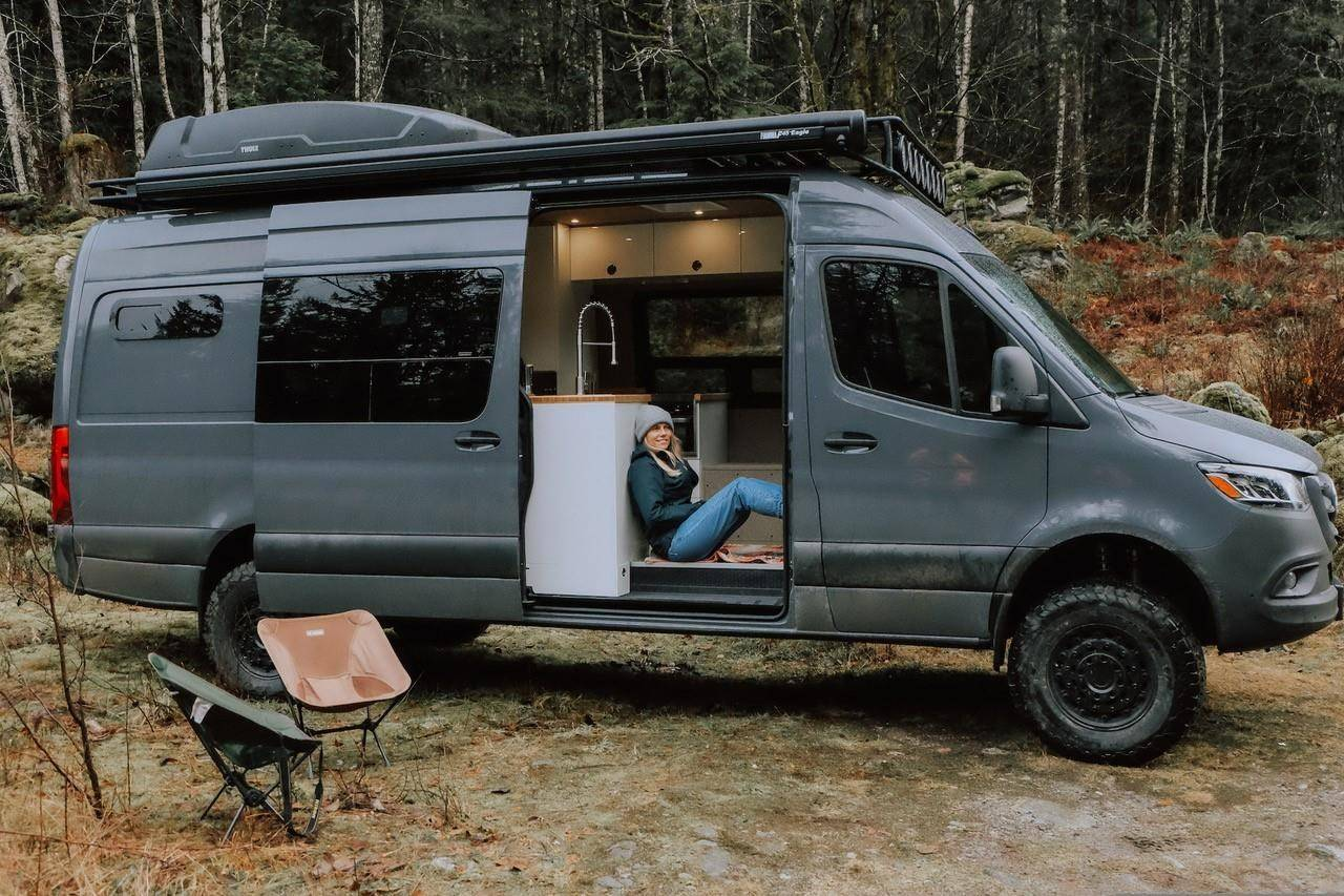 Hilary Shandonay, an employee of Pura Vida Vans, sits in a converted van. (THE CANADIAN PRESS)