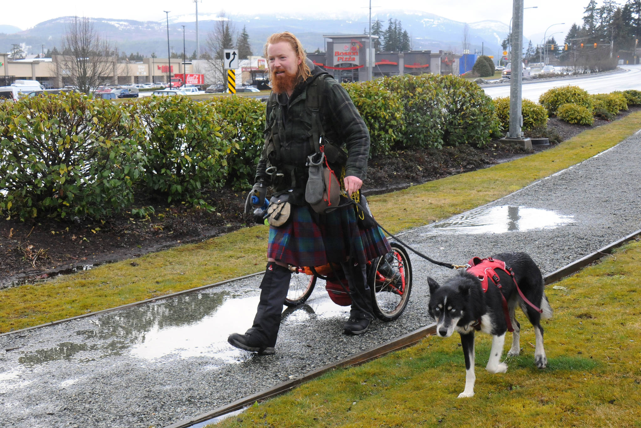 Michael Yellowlees and his dog Luna continue on their journey through Port Alberni after a couple of interviews on a soggy Friday, March 5, 2021. Yellowlees left Tofino four days previously and intends to walk to Newfoundland and Labrador to raise awareness for a Scottish environmental charity. (SUSAN QUINN/ Alberni Valley News)