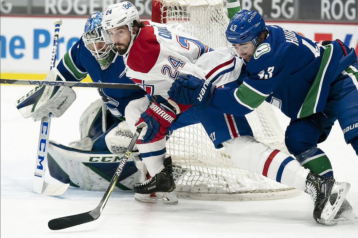 Vancouver Canucks goaltender Thatcher Demko (35) looks on as Montreal Canadiens left wing Phillip Danault (24) battles with Canucks defenceman Quinn Hughes (43) during first-period NHL action in Vancouver, Wednesday, March 10, 2021. THE CANADIAN PRESS/Jonathan Hayward