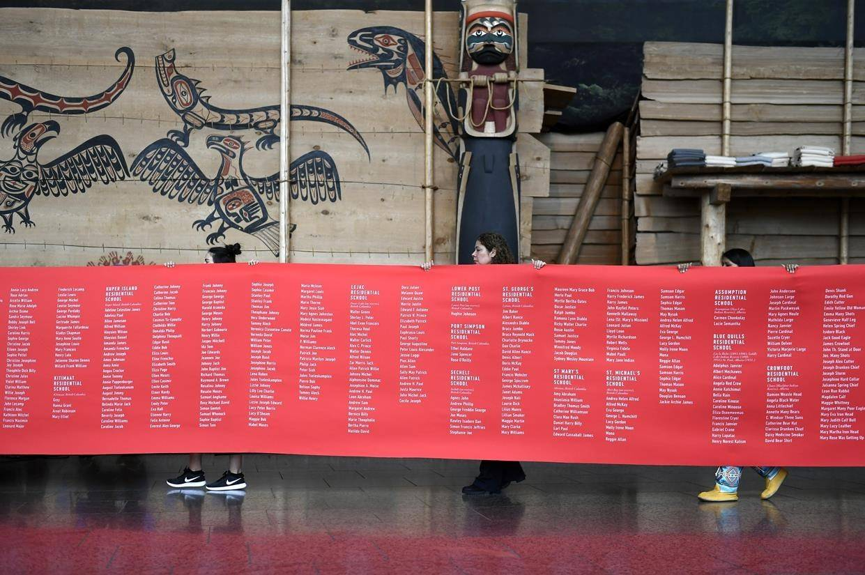 A ceremonial cloth with the names of 2,800 children who died in residential schools and were identified in the National Student Memorial Register, is carried to the stage during the Honouring National Day for Truth and Reconciliation ceremony in Gatineau, Quebec on Monday, Sept. 30, 2019. A new report says more than $3 billion has been paid out to victims of Canada's notorious residential schools. THE CANADIAN PRESS/Justin Tang