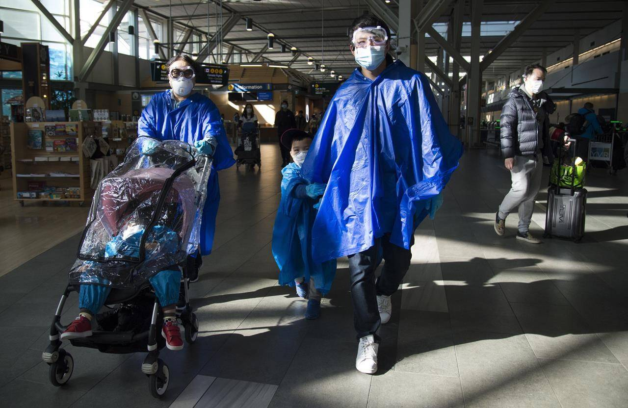 Travellers wearing safety goggles, protective face masks and rain ponchos are seen heading to the international departure gates at Vancouver International Airport in Richmond, B.C. on March 18, 2020. THE CANADIAN PRESS/Jonathan Hayward