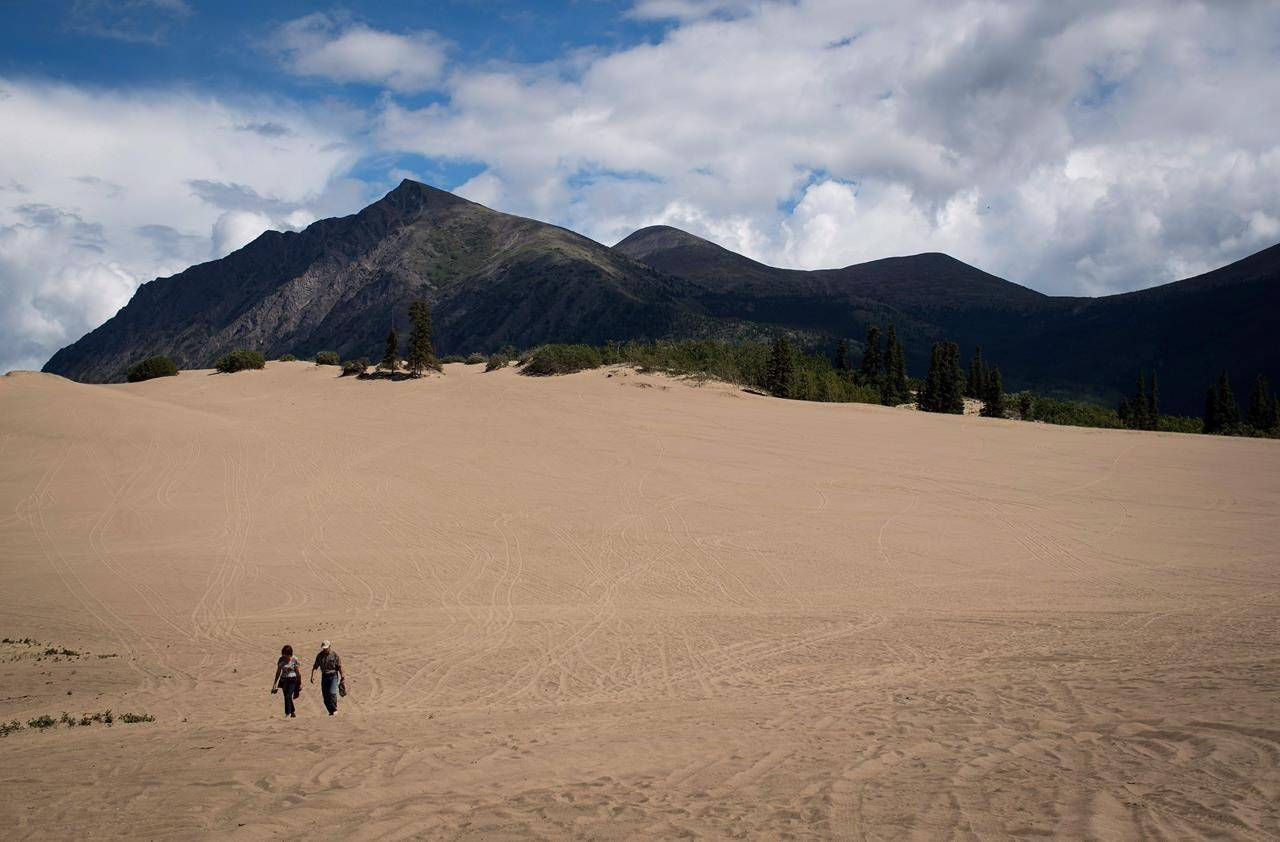 A woman and man walk on the Carcross Dunes in Carcross, Yukon, on Monday, July 2, 2018. THE CANADIAN PRESS/Darryl Dyck