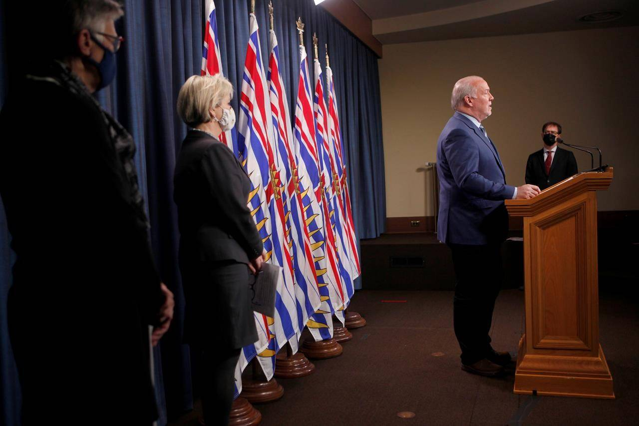 Premier John Horgan speaks about Phase 2 in B.C.'s COVID-19 immunization plan as Dr. Penny Ballem, far left, Dr. Bonnie Henry and Minister Adrian Dix look on during a press conference at Legislature in Victoria, B.C., on Monday, March 1, 2021. THE CANADIAN PRESS/Chad Hipolito