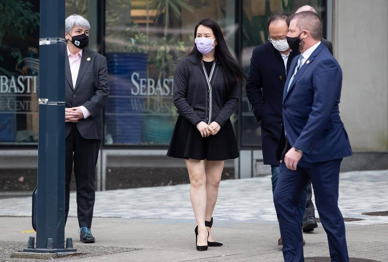 Meng Wanzhou, centre, chief financial officer of Huawei, walks back to B.C. Supreme Court after a lunch break, in Vancouver, on Thursday, March 4, 2021. THE CANADIAN PRESS/Darryl Dyck