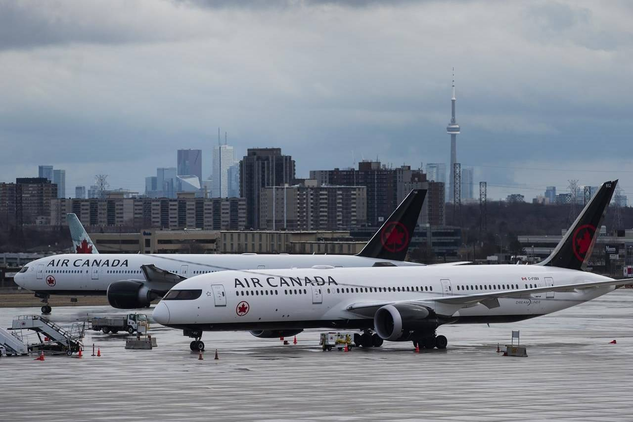 Air Canada airplanes sit on the tarmac at Pearson International Airport in Toronto on Friday, March 20, 2020. THE CANADIAN PRESS/Nathan Denette