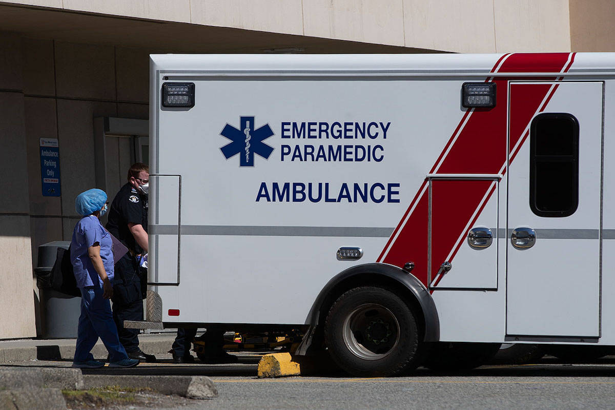 A healthcare worker watches as a B.C. Ambulance Service paramedic moves a patient into an ambulance outside the emergency department at Royal Columbian Hospital in New Westminster, B.C., on Sunday, April 12, 2020. THE CANADIAN PRESS/Darryl Dyck