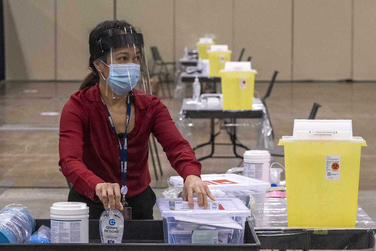 Toronto Public Health nurse Lalaine Agarin makes preparations at Toronto's mass vaccination clinic, Jan. 17, 2021. Community clinics open across B.C. Monday, March 14. THE CANADIAN PRESS/Frank Gunn