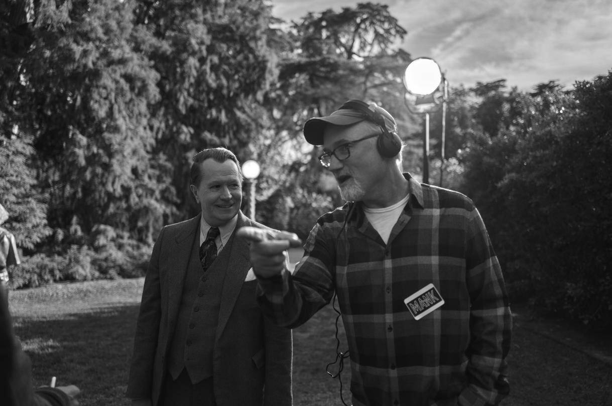 """In this image released by Netflix, actor Gary Oldman, left, appears with director and David Fincher on the set of """"Mank."""" (Netflix via AP)"""