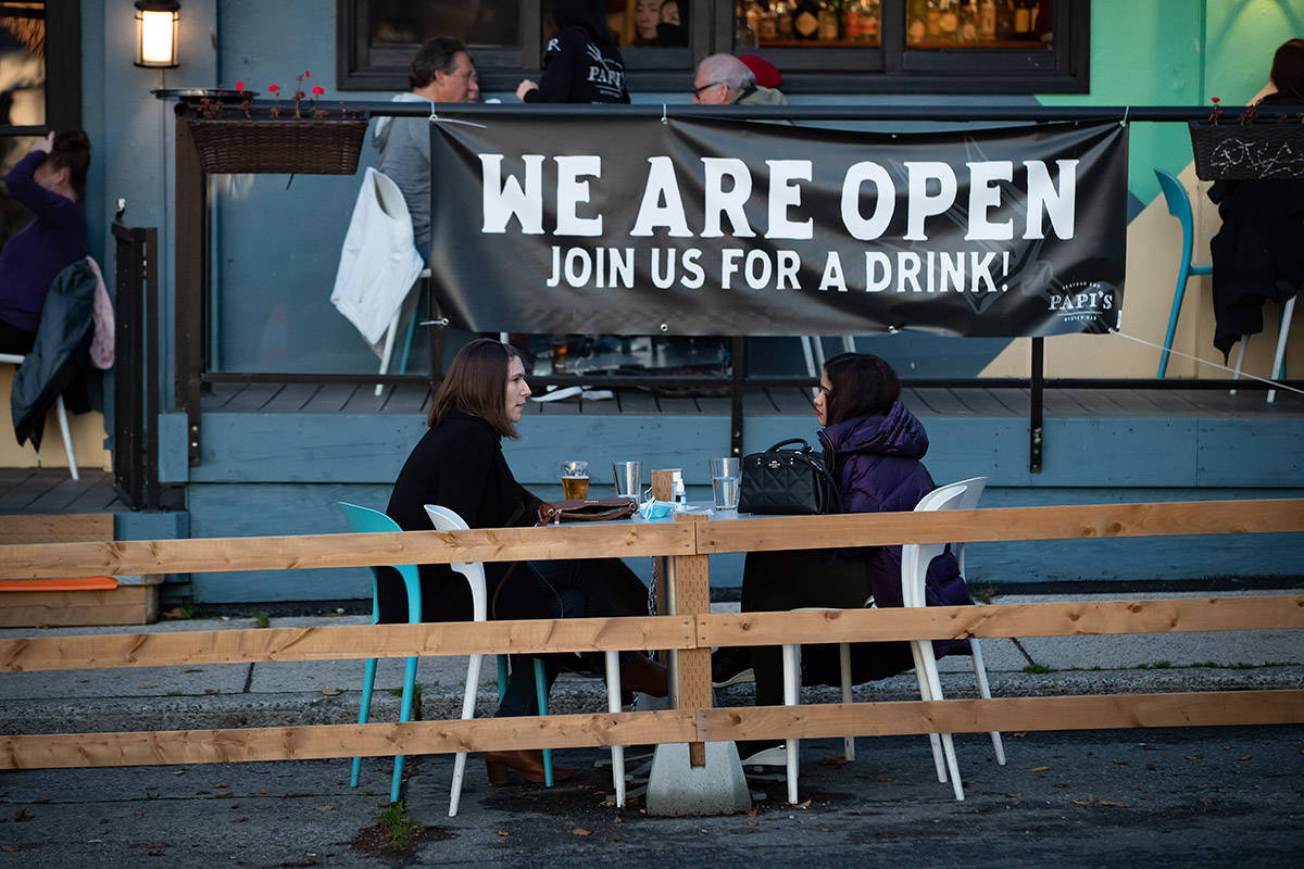 FILE – People sit at a table on a temporary street patio allowed due to the COVID-19 pandemic, outside a restaurant and bar in Vancouver, on Saturday, November 28, 2020. THE CANADIAN PRESS/Darryl Dyck