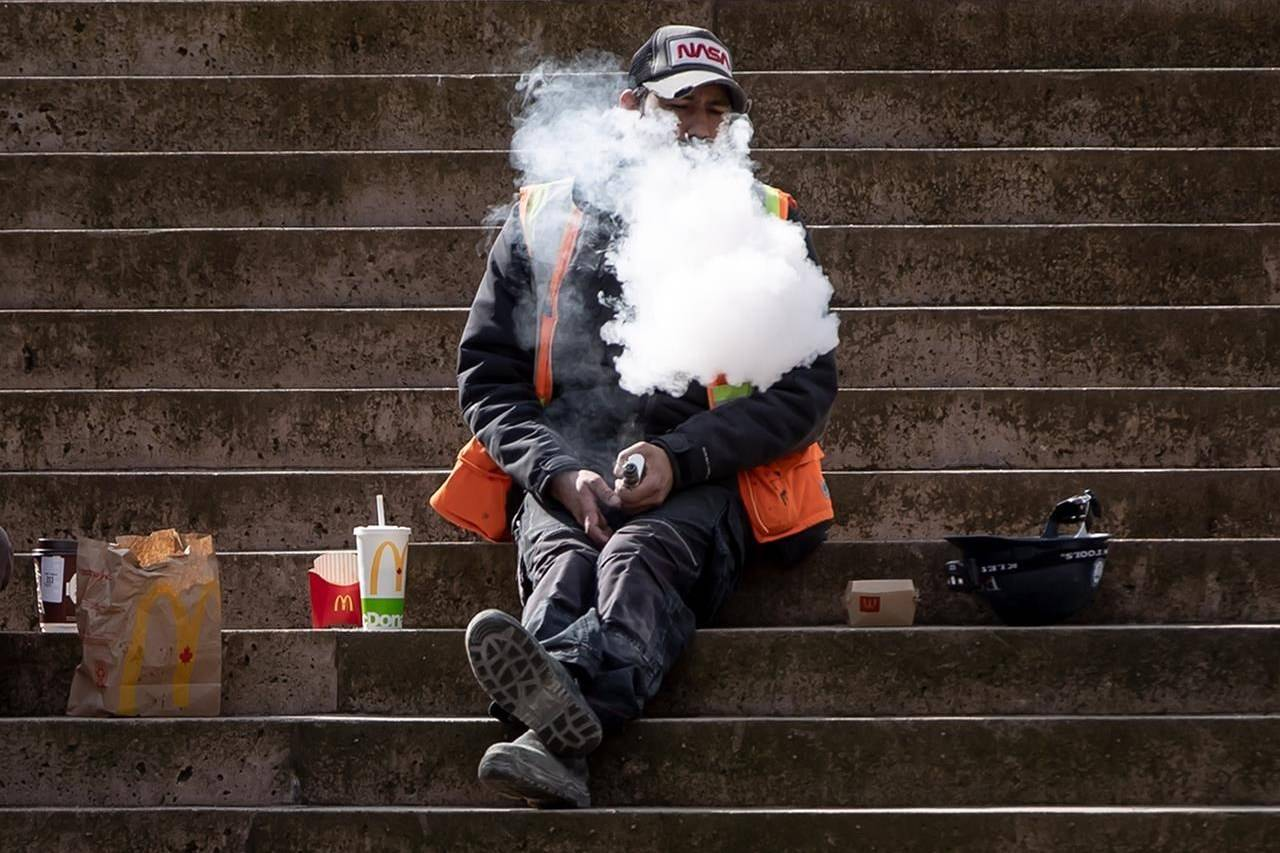 A construction worker exhales after using a vaping device while eating lunch on the steps at Robson Square, in Vancouver, on Monday, March 8, 2021. THE CANADIAN PRESS/Darryl Dyck
