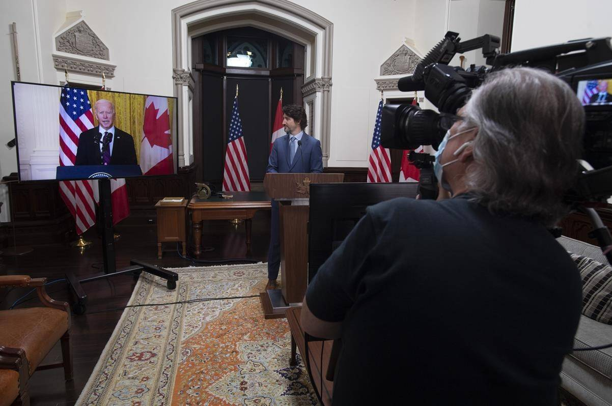 A cameraman records as Canadian Prime Minister Justin Trudeau and United States President Joe Biden participate in a virtual joint statement in Ottawa on February 23, 2021. THE CANADIAN PRESS/Adrian Wyld