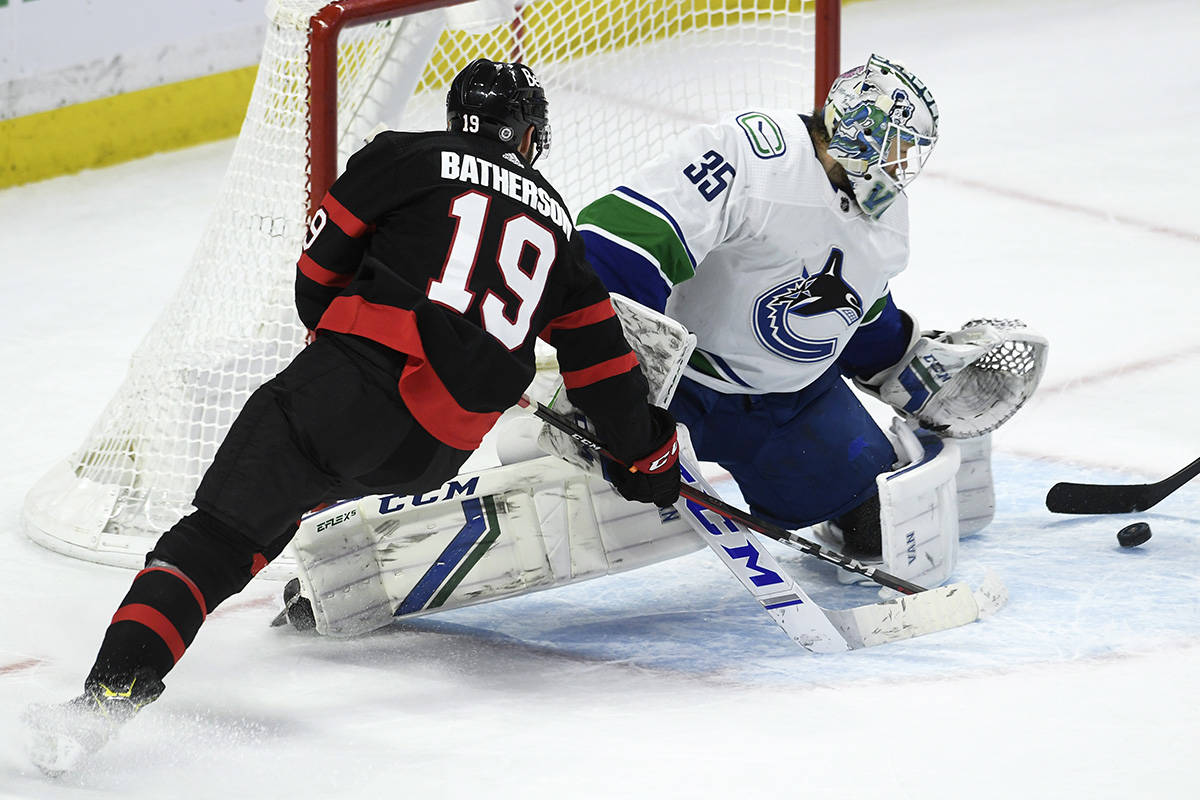 Vancouver Canucks goaltender Thatcher Demko pushes aside the puck on an effort to score by Ottawa Senators right wing Drake Batherson during second period NHL action Wednesday, March 17, 2021 in Ottawa. THE CANADIAN PRESS/Adrian Wyld