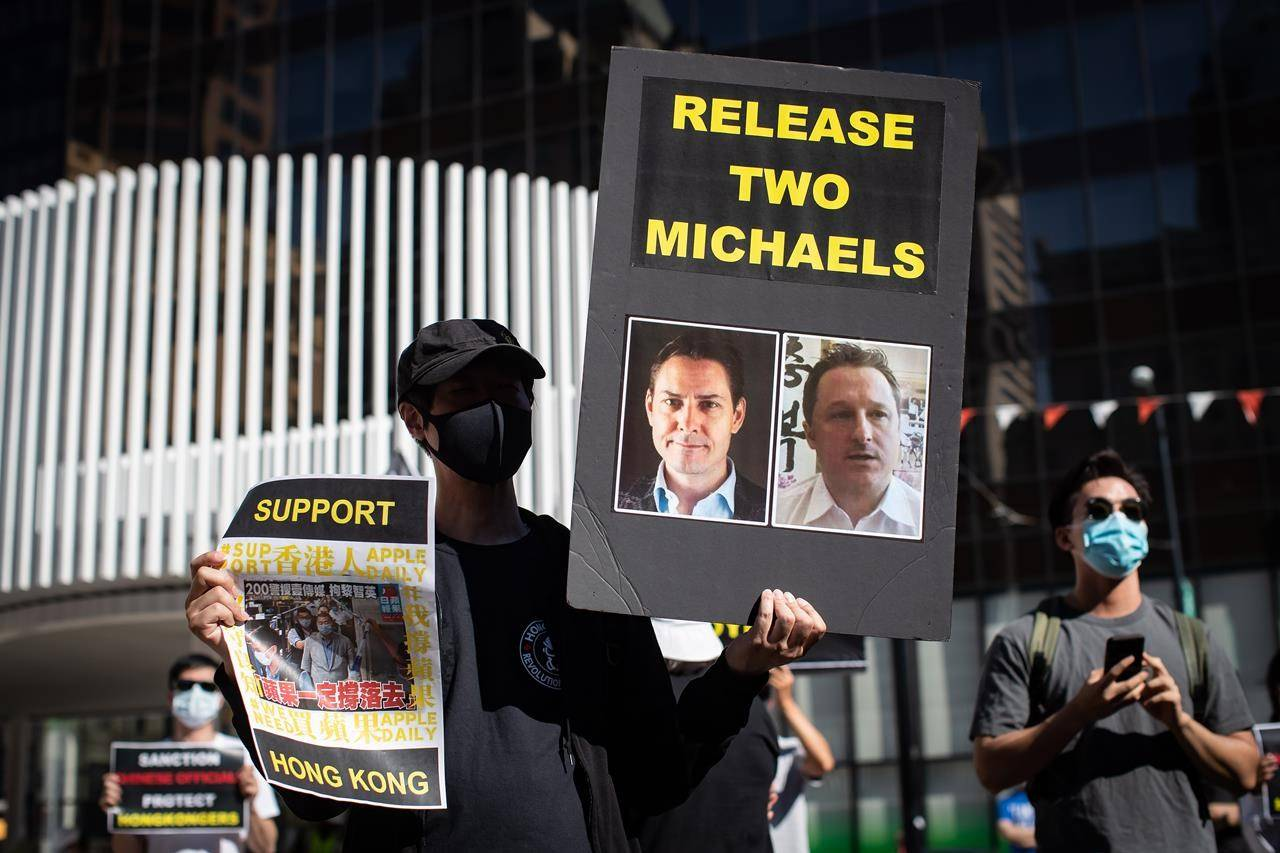 A person holds a sign with photographs of Michael Kovrig and Michael Spavor, who have been detained in China since December, 2018, as people gather for a rally in Vancouver, B.C., Sunday, Aug. 16, 2020. China is defending the way it has handled the cases of two Canadians who have been detained in the country for more than two years. THE CANADIAN PRESS/Darryl Dyck