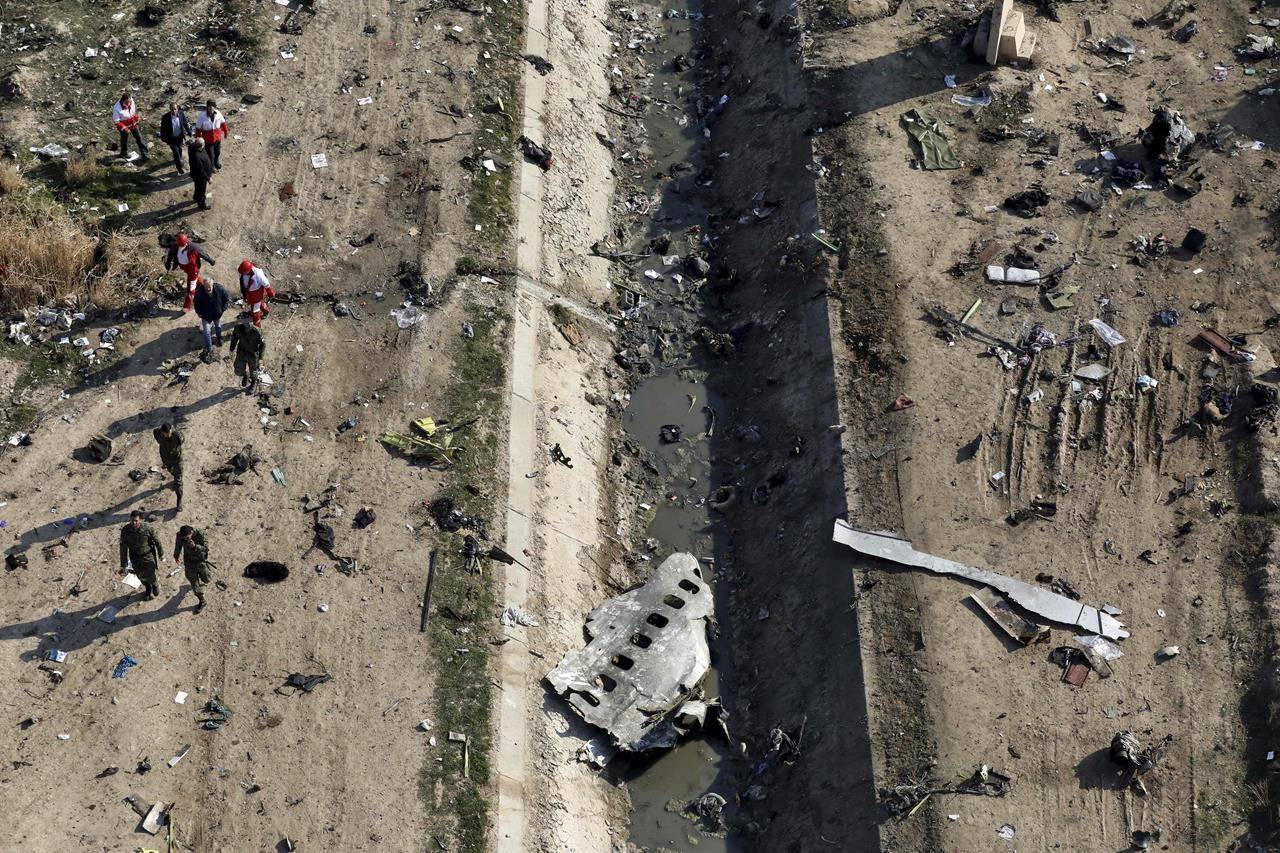 """In this Wednesday, Jan. 8, 2020 photo, rescue workers search the scene where a Ukrainian plane crashed in Shahedshahr, southwest of the capital Tehran, Iran. Canada's Transportation Safety Board says it will comment this morning on a report from Iran on the downing of a passenger jet by its military in January 2020. The final report blames """"human error"""" as the reason why Iran's Revolutionary Guard shot down Ukraine International Airlines Flight 752 minutes after it took off from Tehran on Jan. 8 last year. THE CANADIAN PRESS/AP-Ebrahim Noroozi"""