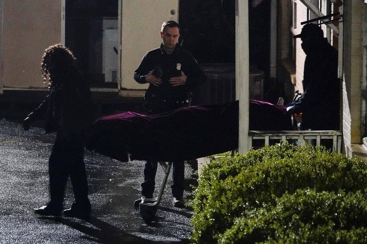 A police officer watches as a body is taken from the Gold Spa massage parlor after a shooting, late Tuesday, March 16, 2021, in Atlanta. Shootings at two massage parlors in Atlanta and one in the suburbs left multiple people dead, many of them women of Asian descent, authorities said. (AP Photo/Brynn Anderson)