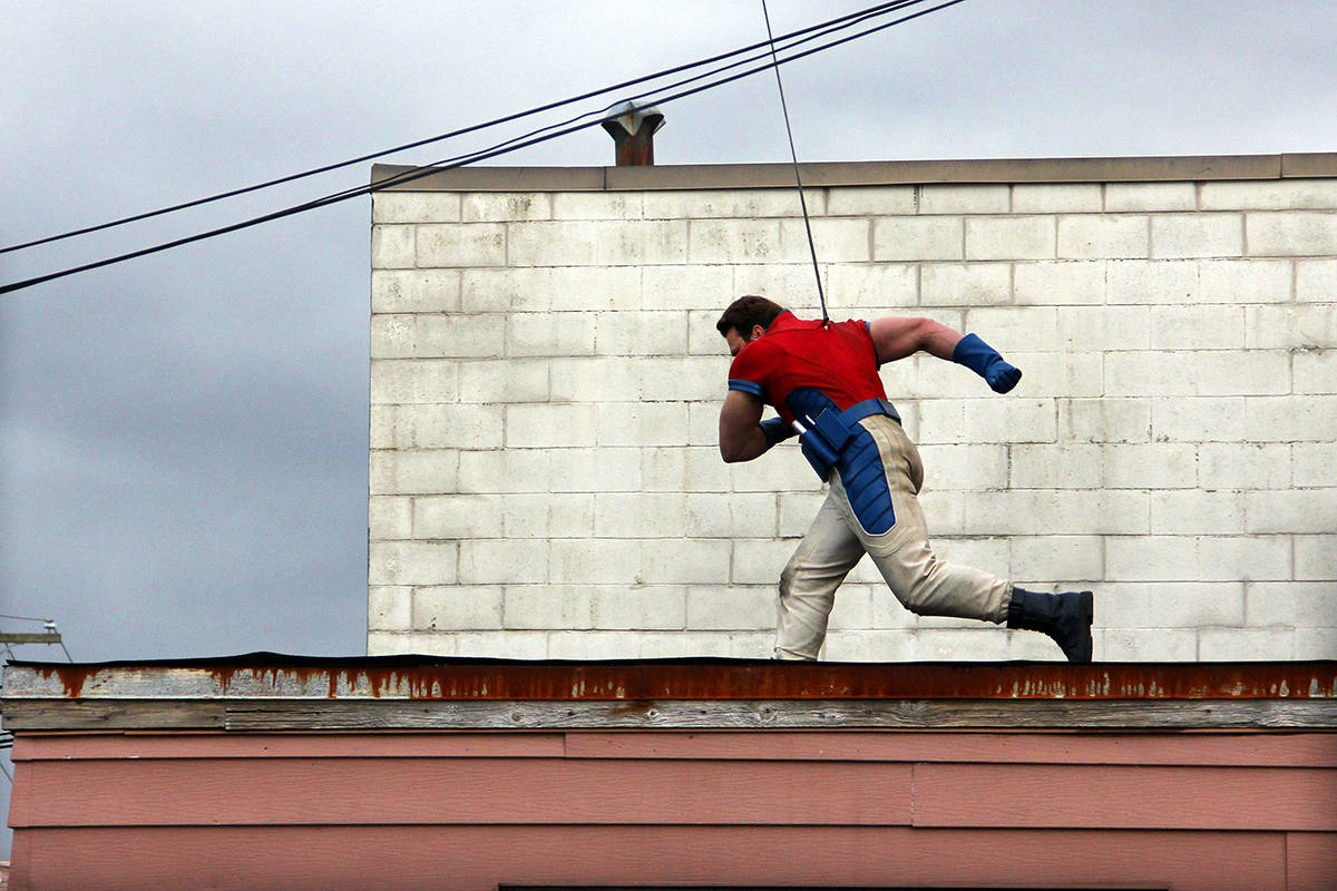 An unknown stuntman leaps out a window on the second of floor of the Dann's Electronics building in Cloverdale March 19. (Photo: Malin Jordan)