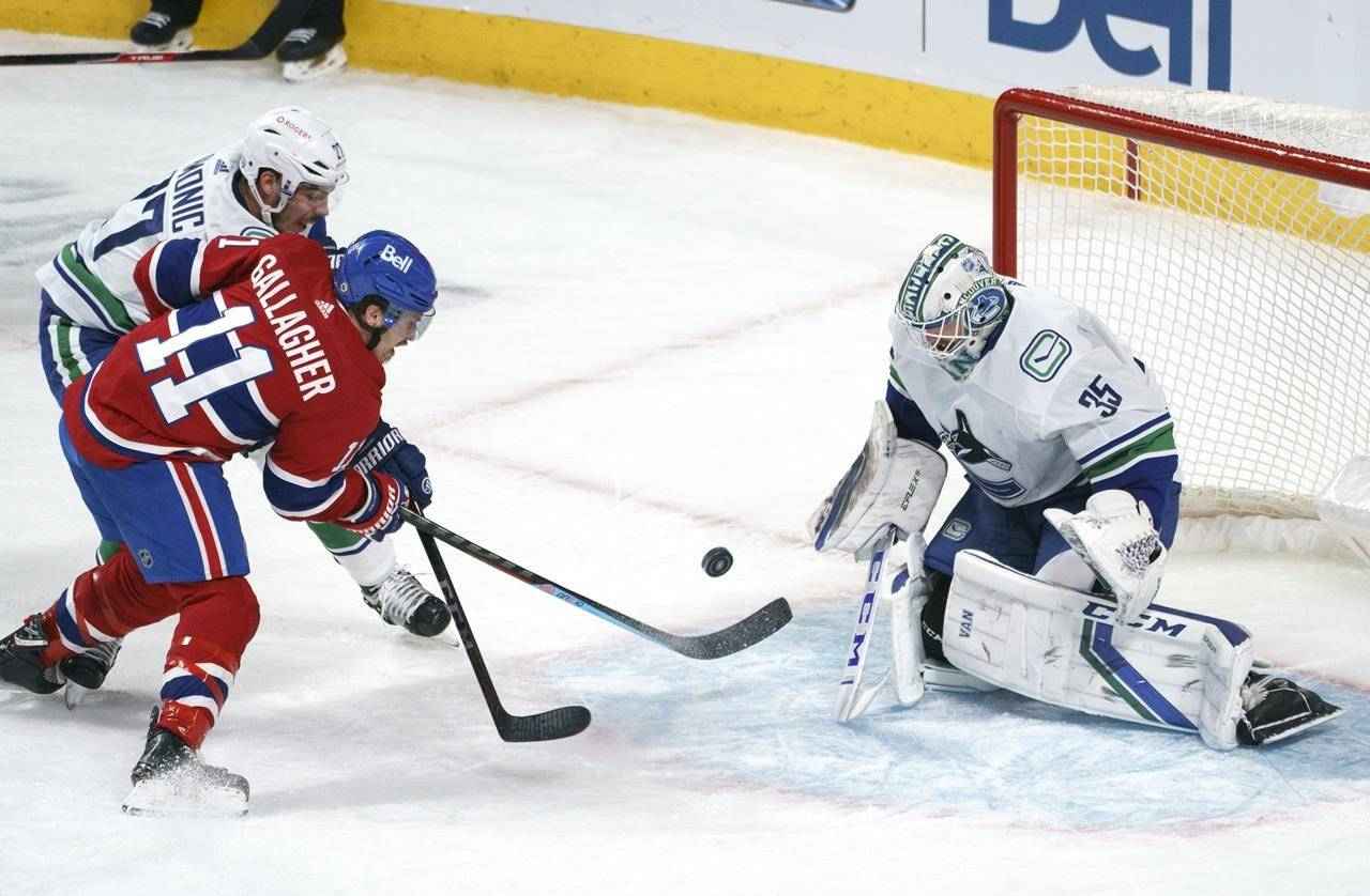 Vancouver Canucks goaltender Thatcher Demko stops Montreal Canadiens' Brendan Gallagher as he is covered by defenceman Travis Hamonic during second-period NHL hockey action in Montreal on Friday, March 19, 2021. THE CANADIAN PRESS/Paul Chiasson