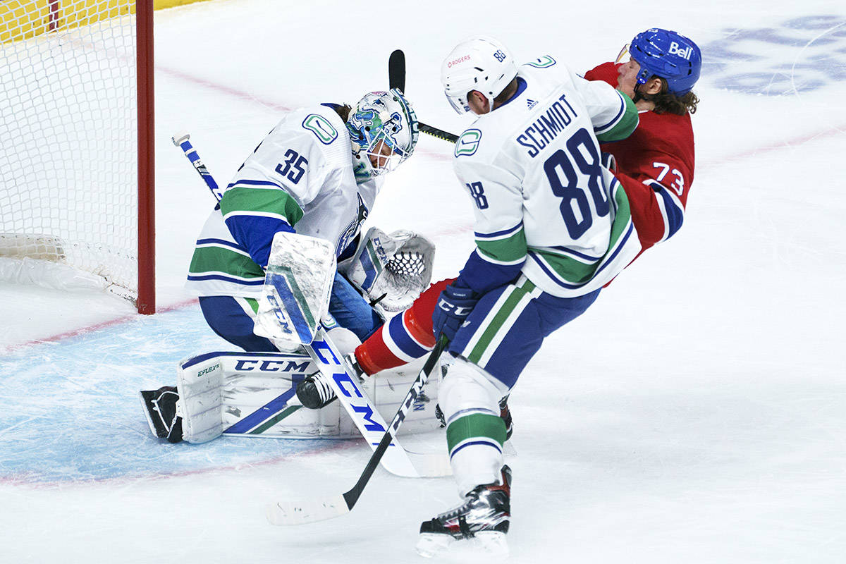 Montreal Canadiens' Tyler Toffoli is taken out from in front of Vancouver Canucks goaltender Thatcher Demko by defenceman Nate Schmidt during first period NHL hockey action in Montreal on Friday, March 19, 2021. THE CANADIAN PRESS/Paul Chiasson