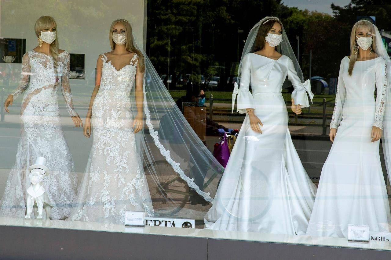 The window of a wedding dress store with mannequins wearing face masks on Thursday, April 23, 2020. The store is closed because of COVID-19 lockdown. THE CANADIAN PRESS/AP-Darko Bandic