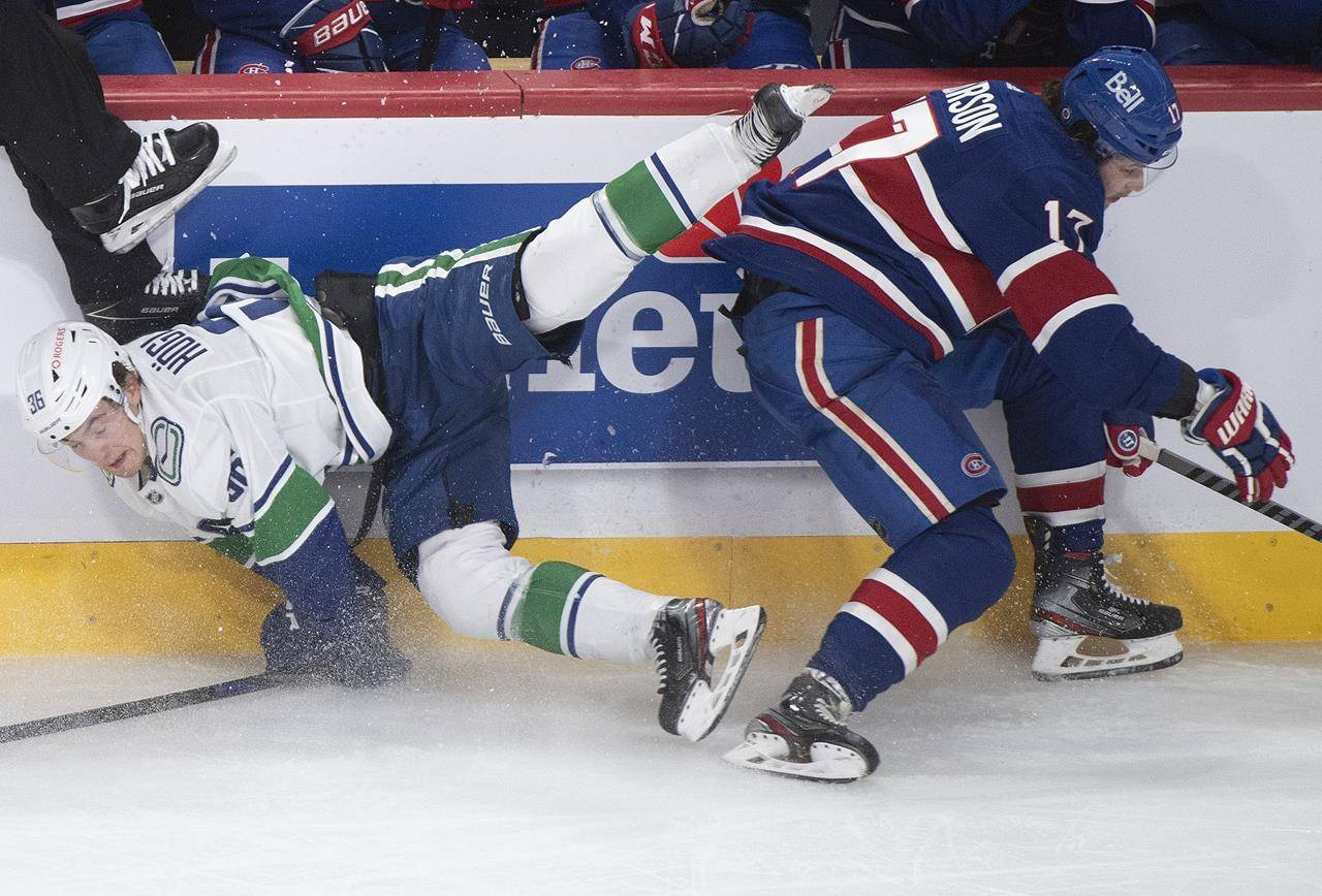 Montreal Canadiens' Josh Anderson (17) checks Vancouver Canucks' Nils Hoglander into the boards during third period NHL hockey action in Montreal, Saturday, March 20, 2021. THE CANADIAN PRESS/Graham Hughes