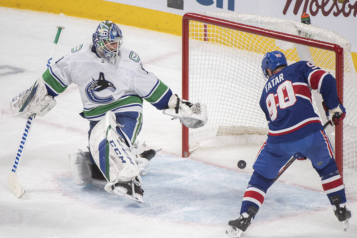 Montreal Canadiens' Tomas Tatar puts the puck in the net behind Vancouver Canucks goaltender Braden Holtby during second period NHL hockey action in Montreal, Saturday, March 20, 2021. THE CANADIAN PRESS/Graham Hughes
