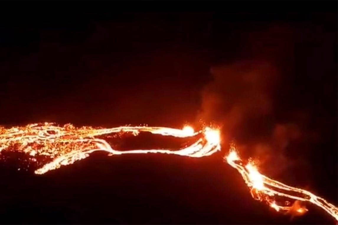 This photo provided by the Icelandic Met Office shows an eruption, center right, on the Reykjanes Peninsula in southwestern Iceland on Friday, March 19, 2021. The long dormant volcano flared to life Friday night, spilling lava down two sides in that area's first volcanic eruption in nearly 800 years. (Icelandic Met Office via AP)