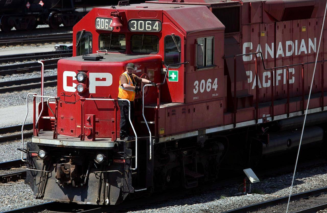 A Canadian Pacific Railway employee walks along the side of a locomotive in a marshalling yard in Calgary on May 16, 2012. THE CANADIAN PRESS/Jeff McIntosh