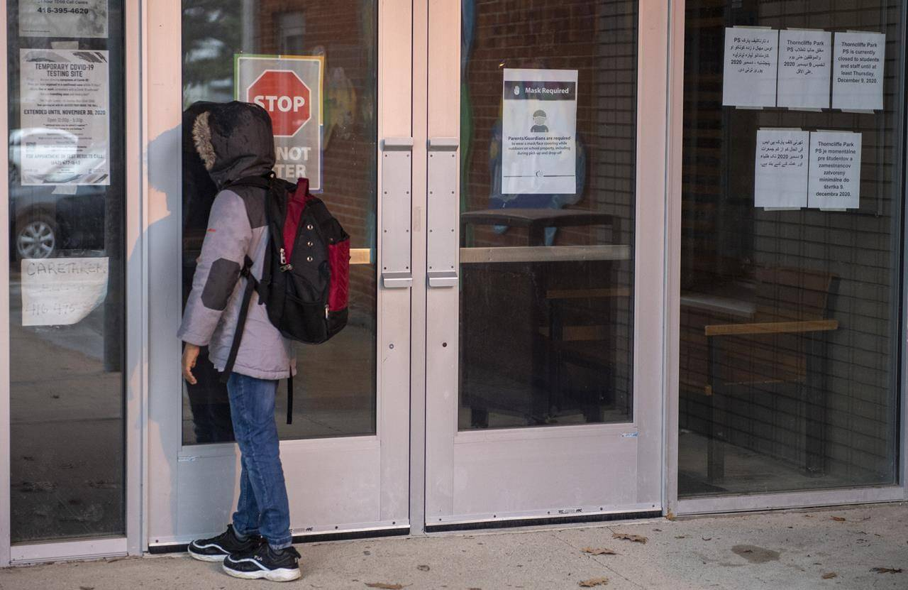 A student peers through the front door of Thorncliffe Park Public School in Toronto on Friday December 4, 2020. THE CANADIAN PRESS/Frank Gunn