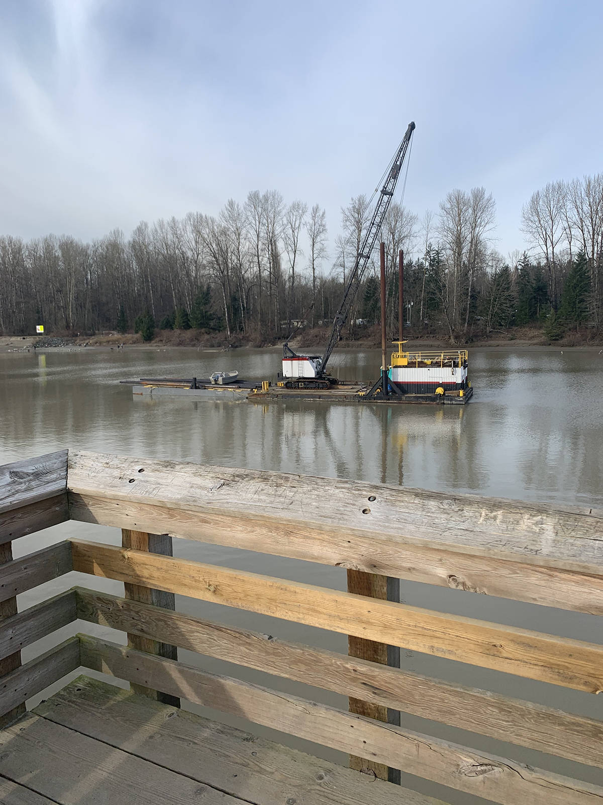 A floating crane moved into position on March 12 to begin work on rebuilding the Fraser River view platform on the Fort to Fort Trail in Langley (Special to Langley Advance Times)