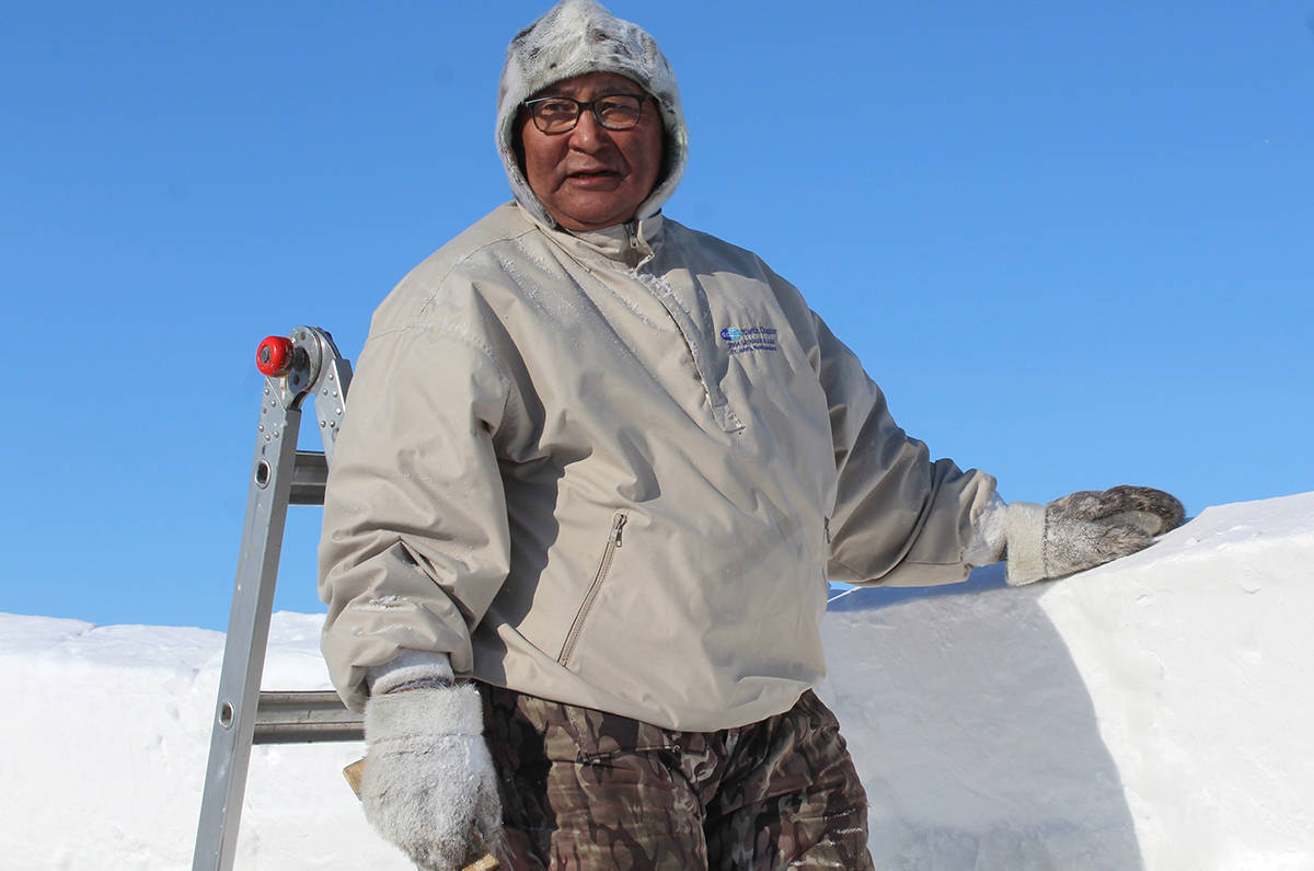 Master igloo-builder Solomon Awa waits to be passed another block of snow on the third day of building a 700 square-foot igloo in Iqaluit, Nunavut on Thursday March 18, 2021. THE CANADIAN PRESS/Emma Tranter