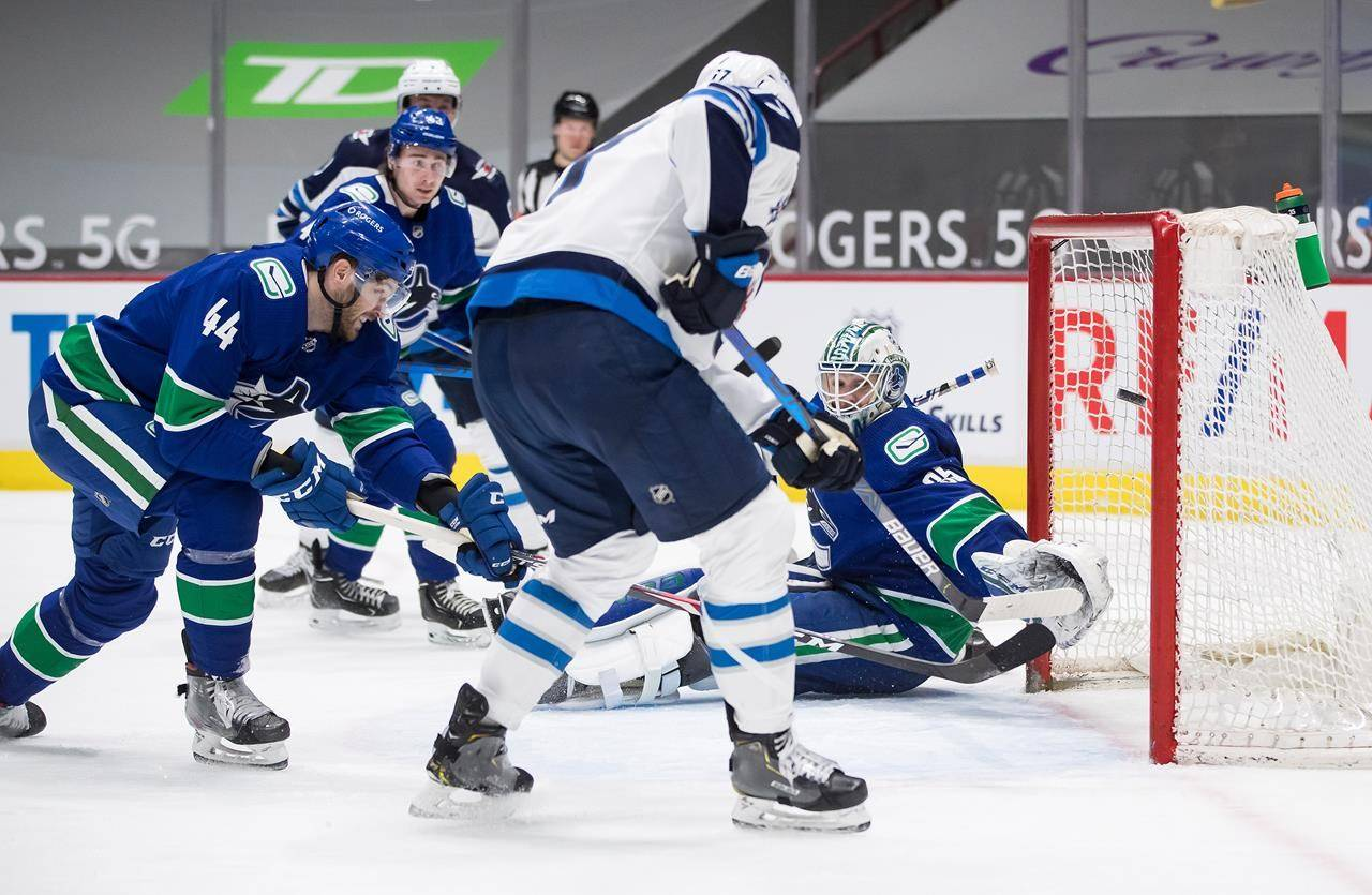 Winnipeg Jets' Adam Lowry, front right, scores his second goal against Vancouver Canucks goalie Thatcher Demko (35) as Tyler Graovac (44) defends during the third period of an NHL hockey game in Vancouver, B.C., Monday, March 22, 2021. THE CANADIAN PRESS/Darryl Dyck