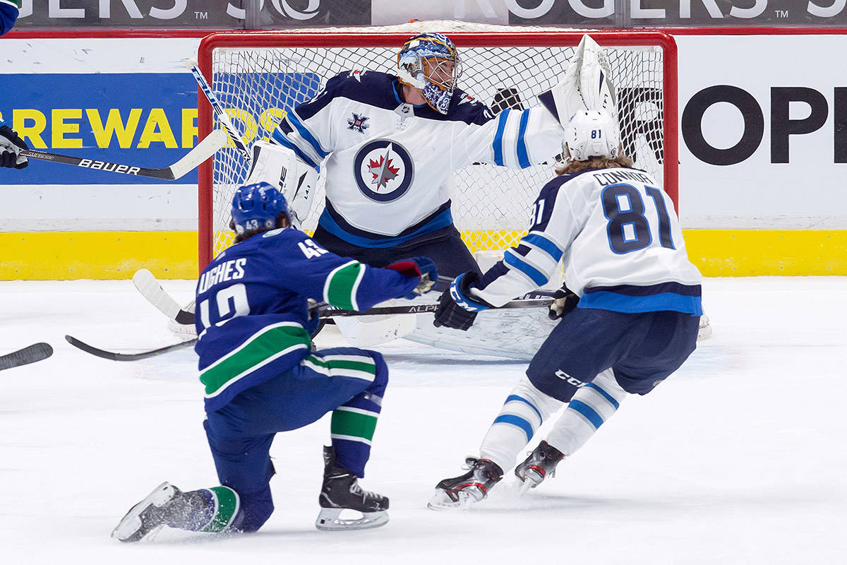 Winnipeg Jets goalie Connor Hellebuyck, top, reaches for a shot by Vancouver Canucks' Quinn Hughes (43) as Winnipeg's Kyle Connor (81) watches during the first period of an NHL hockey game in Vancouver, B.C., Monday, March 22, 2021. THE CANADIAN PRESS/Darryl Dyck