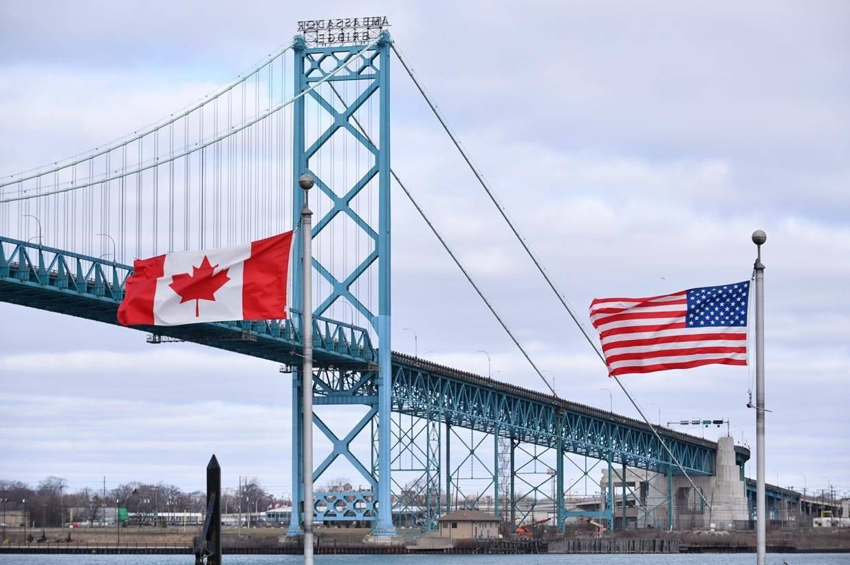 Canadian and American flags fly near the Ambassador Bridge at the Canada/U.S. border crossing in Windsor, Ont. on Saturday, March 21, 2020. THE CANADIAN PRESS/Rob Gurdebeke