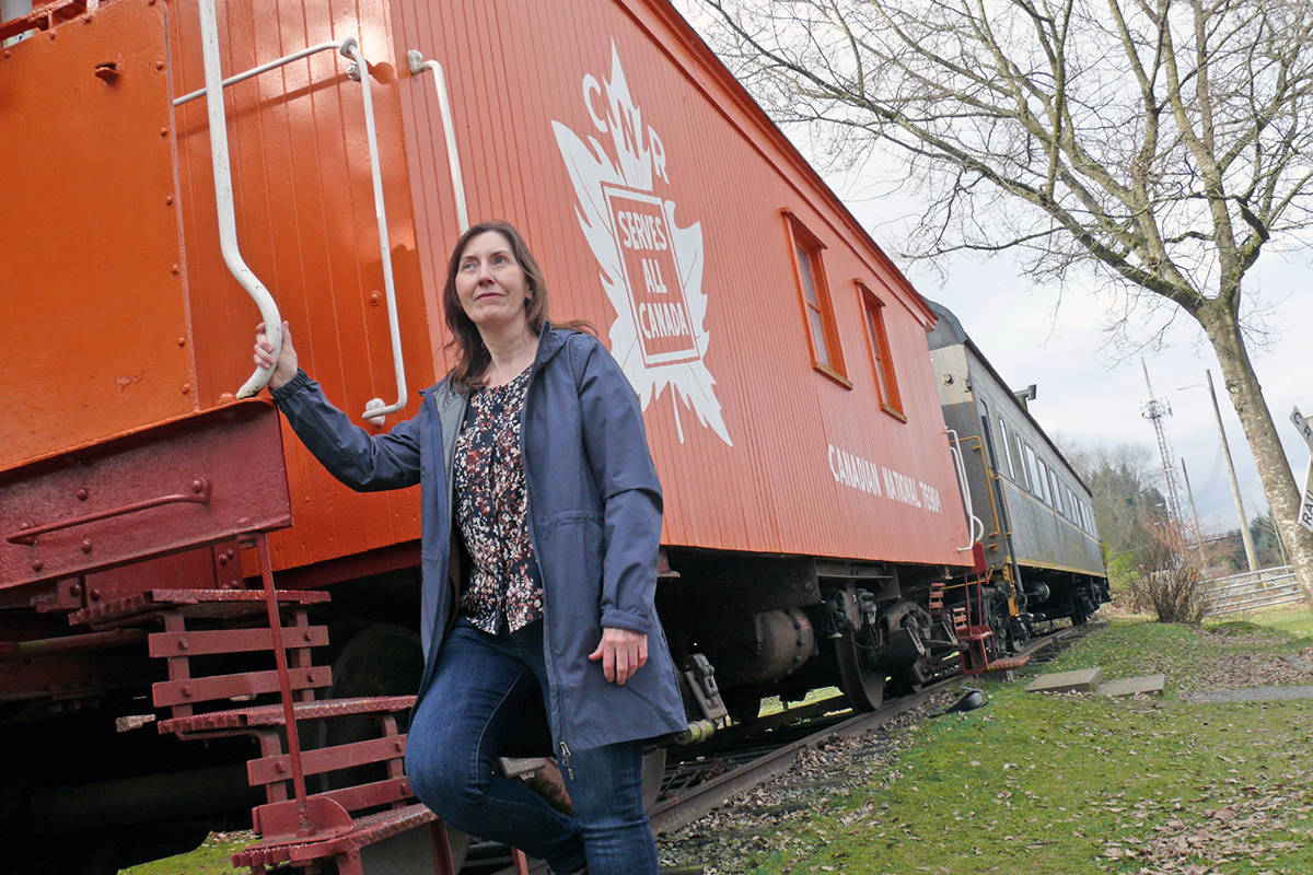 Helen Williams, manager of the heritage CN station in Fort Langley, is seen on Tuesday, March 23, next to the antique rolling stock that is a regular target of taggers and people climbing up on the roofs of the century-old cars (Dan Ferguson/Langley Advance Times)