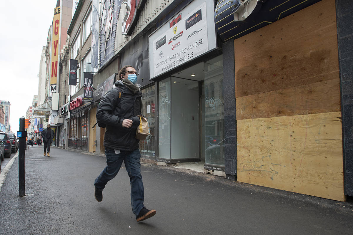 People wear masks as they walk past closed storefronts downtown as COVID-19 continues to take an economic toll Thursday, March 18, 2021 in Montreal. THE CANADIAN PRESS/Ryan Remiorz