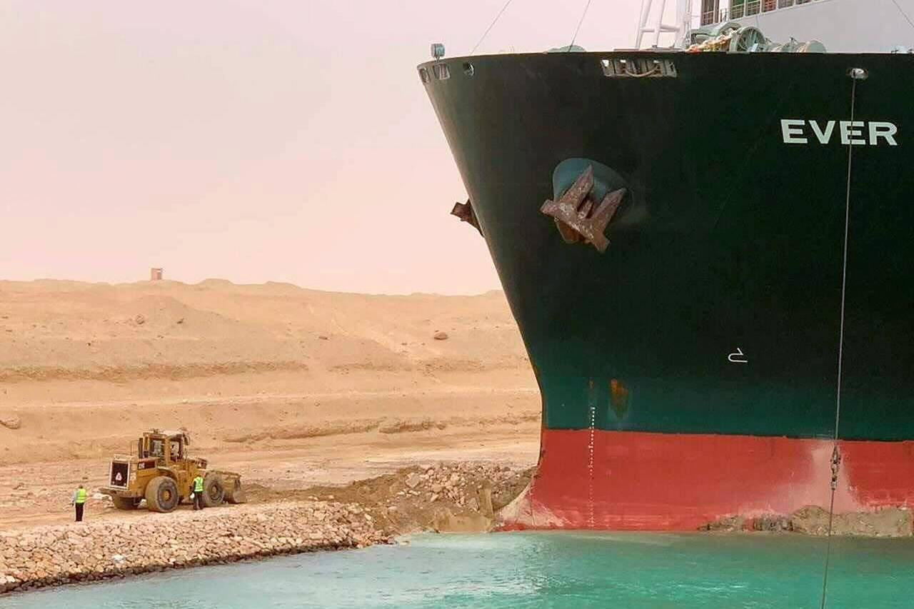 In this photo released by the Suez Canal Authority, a cargo ship, named the MV Ever Given, sits with its bow stuck into the wall Wednesday, March 24, 2021, after it turned sideways in Egypt's Suez Canal, blocking traffic in a crucial East-West waterway for global shipping. An Egyptian official warned Wednesday it could take at least two days to clear the ship. (Suez Canal Authority via AP)