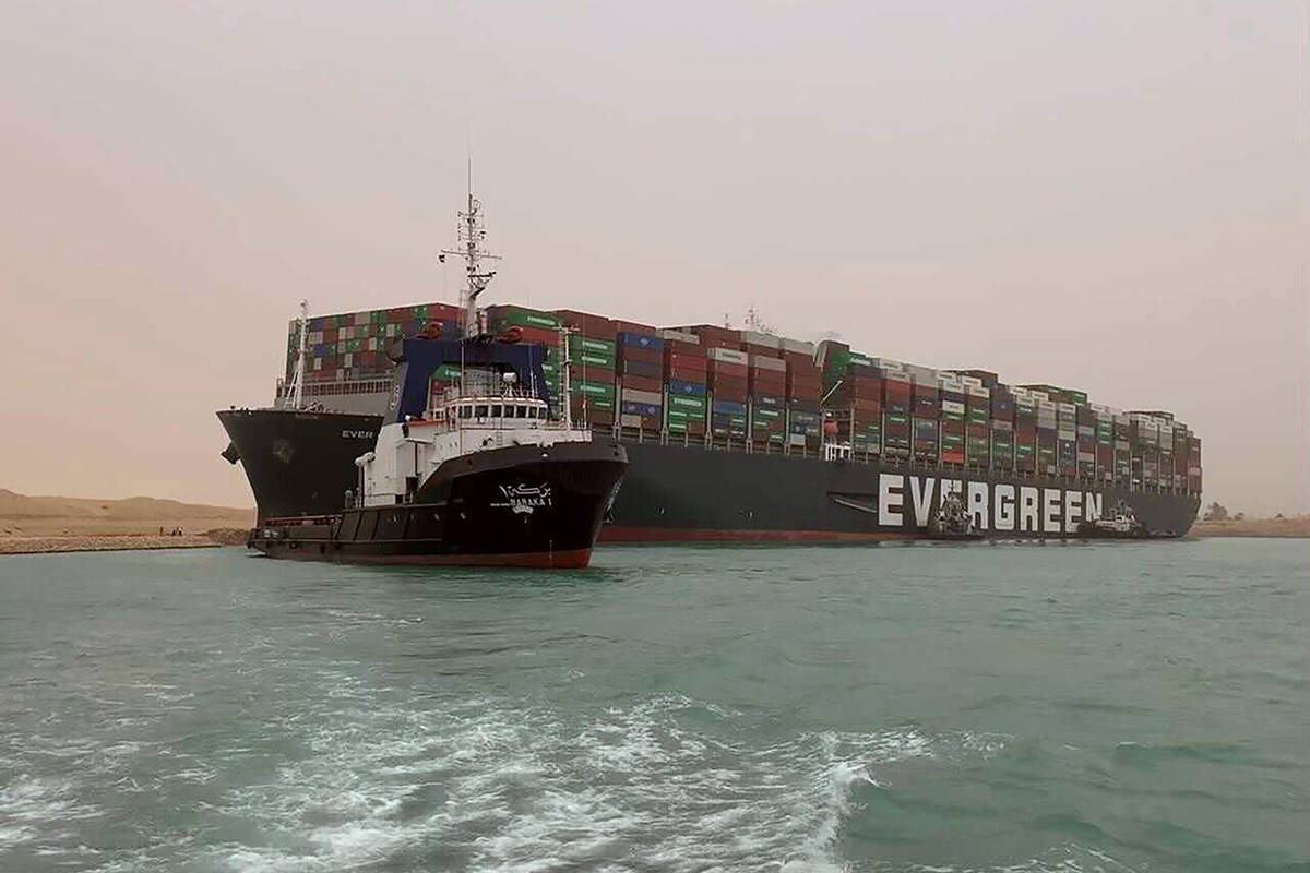 In this photo released by the Suez Canal Authority, a boat navigates in front of a massive cargo ship, named the MV Ever Given, rear, sits grounded Wednesday, March 24, 2021, after it turned sideways in Egypt's Suez Canal, blocking traffic in a crucial East-West waterway for global shipping. An Egyptian official warned Wednesday it could take at least two days to clear the ship. (Suez Canal Authority via AP)