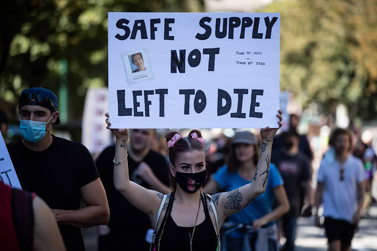 A woman holds up a sign bearing a photograph of Morgan Goodridge during a memorial march to remember victims of overdose deaths in Vancouver on Saturday, August 15, 2020. THE CANADIAN PRESS/Darryl Dyck