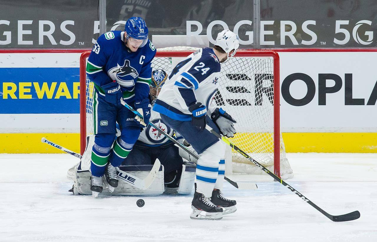 Vancouver Canucks' Bo Horvat (53) is struck by the puck in front of Winnipeg Jets goalie Connor Hellebuyck as Derek Forbort (24) watches during the third period of an NHL hockey game in Vancouver, B.C., Monday, March 22, 2021. THE CANADIAN PRESS/Darryl Dyck