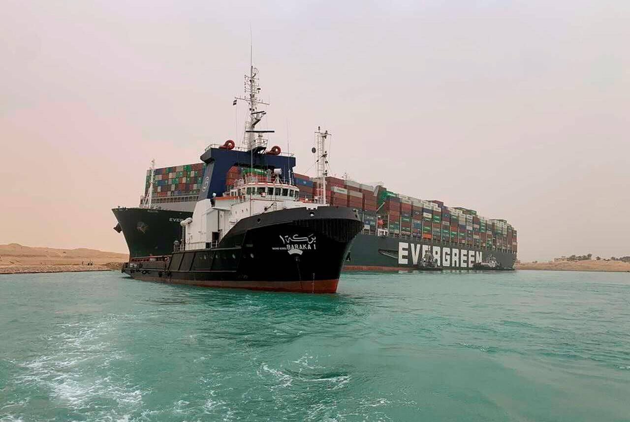 In this photo released by the Suez Canal Authority, a boat navigates in front of a cargo ship, Ever Given, Wednesday, March 24, 2021, after it become wedged across Egypt's Suez Canal and blocked all traffic in the vital waterway. An Egyptian official warned Wednesday it could take at least two days to clear the ship. THE CANADIAN PRESS/Suez Canal Authority via AP
